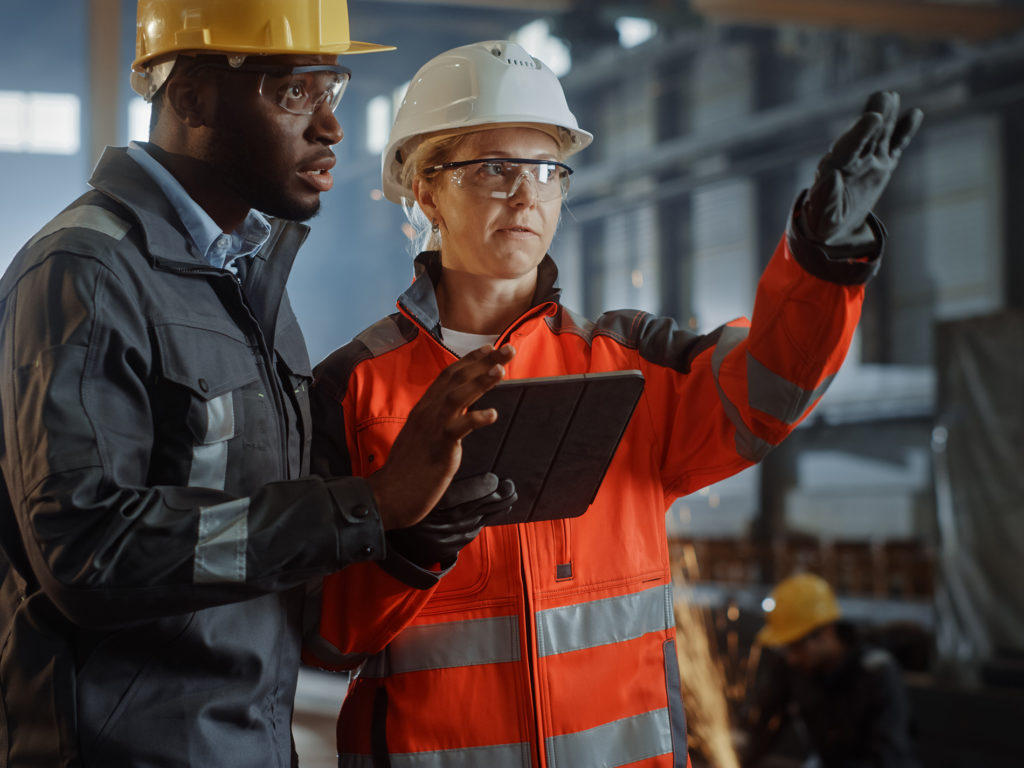 Two Heavy Industry Engineers Stand in Steel Metal Manufacturing Factory, Use Digital Tablet Computer and Have a Discussion. Black African American Industrial Specialist Talk to Female Technician.