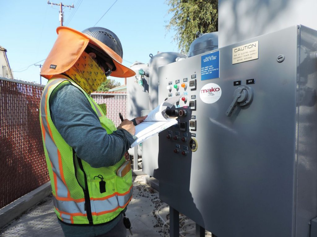 Apex environmental worker with a clip board evaluating a utility box