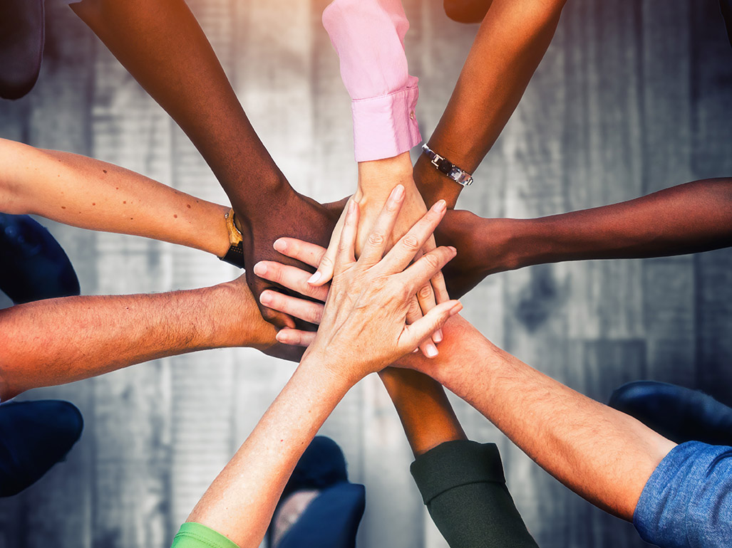 Close up view of diverse people putting their hands together