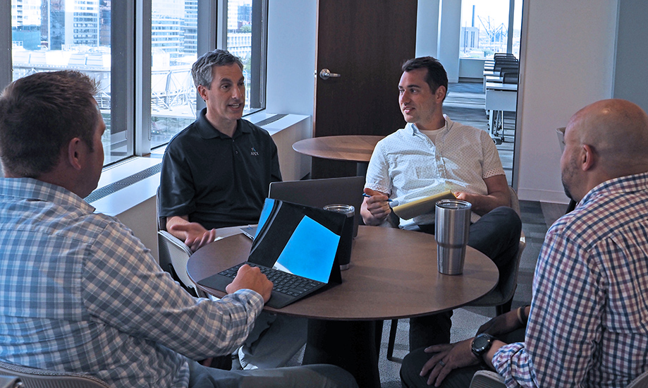 Apex employees in discussion around a table in an office